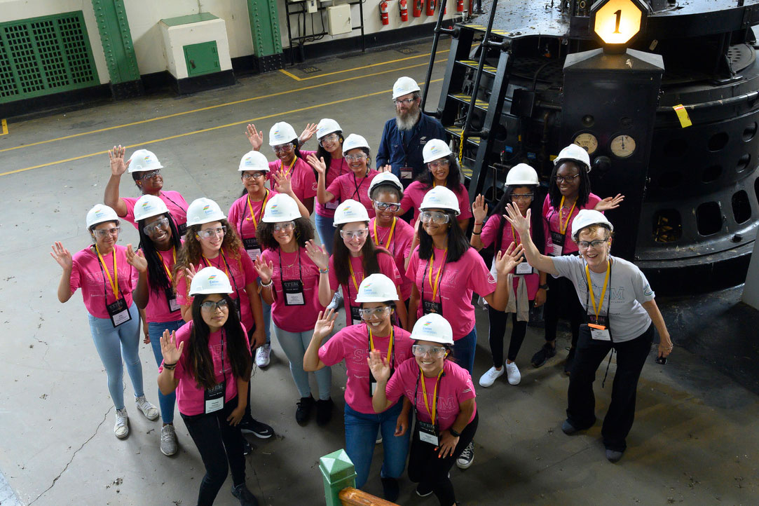 Group of female STEM students in pink shirts and hard hats