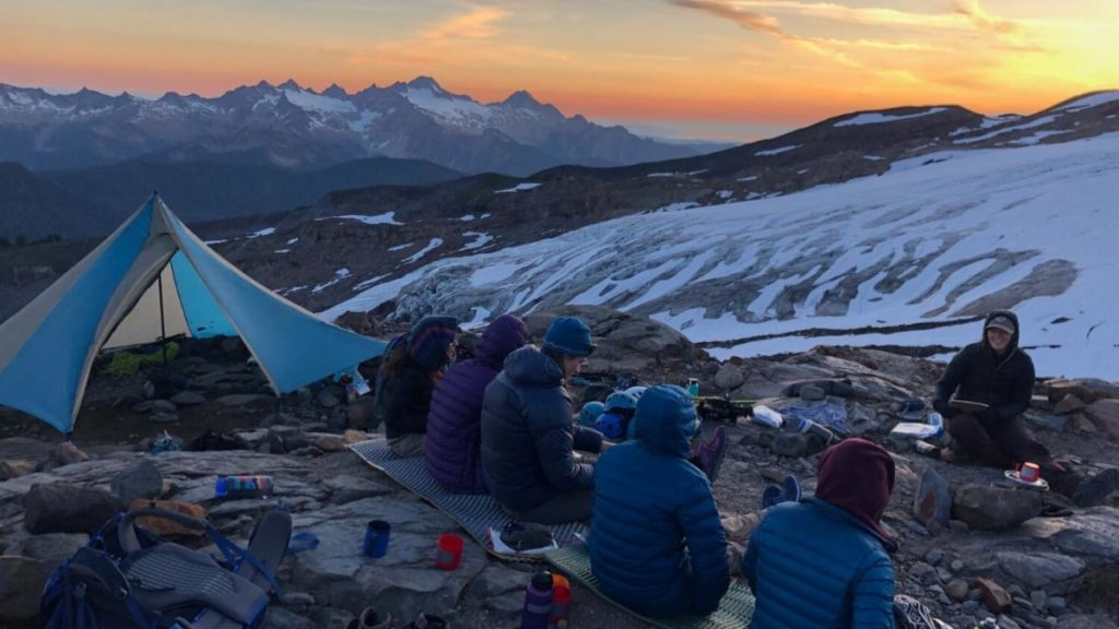 Group of girls and women camping out in a snowy mountain range